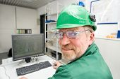 stock photo of workplace safety  - Industrial worker in his office in front of a pc - JPG