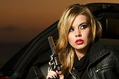 stock photo of revolver  - A sultry blond woman dressed in black is getting out of a red sports car holding a revolver - JPG