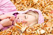 Little Girl Lying In Autumn Leaves