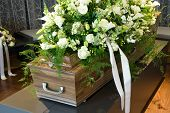 stock photo of crematory  - A coffin in a morgue with a flower arrangement - JPG