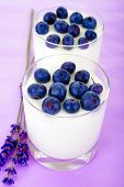 pic of lilas  - Sweet yogurt with blueberry on a lila background - JPG