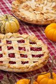 pic of cherry pie  - Cherry pie with lattice top and apple pie on fall themed napkin and mini pumpkins - JPG