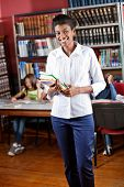 Portrait of happy African American librarian holding books while standing in library with students i