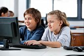 Cute little boy and girl using desktop PC at desk in school computer lab