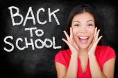 Back to School - university college student teacher screaming excited by blackboard with BACK TO SCHOOL written on chalkboard. Female student or funny woman teacher.