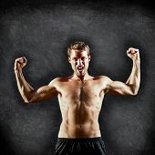Crossfit fitness man flexing strong and aggressive showing muscles on blackboard background with copy space for text. Male cross fitness trainer on chalkboard background showing biceps muscles