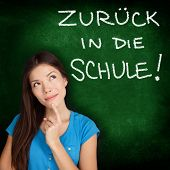 Zuruck in die Schule - German college university student woman thinking Back to School written in German on blackboard by female on green chalkboard. German language at college or high school.
