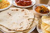 Chapatti roti or chapati, curry chicken, biryani rice, salad, masala milk tea and papadom. Indian fo