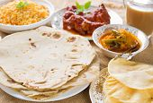 Chapatti roti or Flat bread, curry chicken, biryani rice, salad, masala milk tea and papadom. Indian