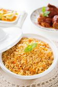 Biryani rice or briyani rice, curry chicken and salad, traditional indian food on dining table.