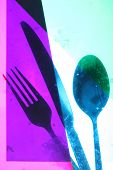 Cutlery taken behind coloured gels to create artistic image. imperfections of gels causing grunge effect. focus is on the image and not the gels so blurring does  occur in parts of the image.