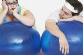 Tired overweight man and woman resting on exercise ball against white background