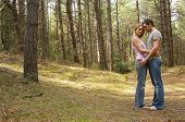 Full length side view of a romantic couple standing in forest