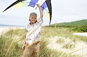 Portrait of happy little boy with arms raised holding kite above head on beach