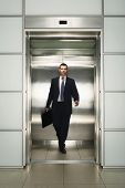 Front view of middle aged businessman with briefcase coming out from elevator
