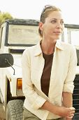 stock photo of four-wheel drive  - Thoughtful middle aged woman standing in front of four - JPG