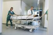 stock photo of overcoats  - Medical workers moving patient on gurney through hospital corridor - JPG