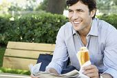 Happy young businessman with sandwich and newspaper looking away while sitting on bench at park