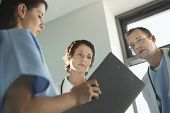 Low angle view of three physicians reviewing medical chart