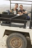 stock photo of four-wheel drive  - Portrait of happy young couple in stationary four - JPG