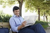 Young businessman reading newspaper while sitting on bench at park