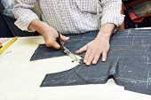 stock photo of tailoring  - Tailor hands working with measure bar - JPG