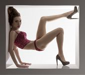 stock photo of doll  - hot portrait of sensual brunette woman fitted like a doll in a small box wearing red lingerie and heels - JPG