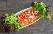 picture of pawpaw  - Thai papaya salad served with lettuce on wood table - JPG