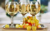White wine in glass on salver on window background