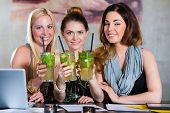 Young women in cafe or restaurant, working or learning together and having fun after business closing time
