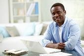 Image of young African man looking at camera with laptop near by