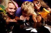 Imagem de cara jovem, cheirando cocaína, rodeada por duas garotas em um clube noturno
