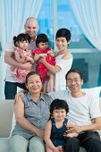 stock photo of kiddie  - Vertical image of a big mixed-race family posing at camera at home