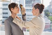 stock photo of strangle  - Businesswoman strangling another who is defending with her shoe in bright office - JPG