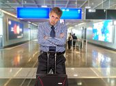 Businessman with a bag on a background of departure board at airport