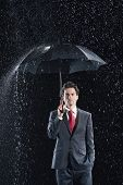 Portrait of a young businessman standing under umbrella in rain against black background