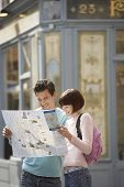Happy young couple reading map on street corner