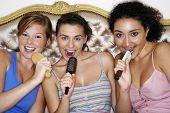 foto of slumber party  - Portrait of teenage girls using brushes as microphones and singing at slumber party - JPG