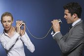stock photo of tin man  - Businessman yelling at female colleague through tin can phone against blue background - JPG