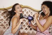 stock photo of slumber party  - Teenage girls playing with brushes and hair dryer at slumber party - JPG