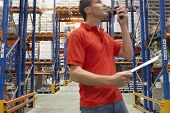 Side view of a warehouse worker using walkie talkie