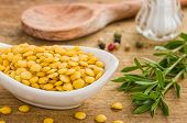Bowl with yellow lentils on a wooden background