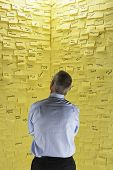 Rear view of a businessman standing in front of wall covered in sticky notes