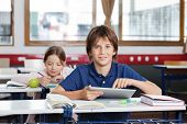 Portrait of cute schoolboy using digital tablet with schoolgirl in background at classroom