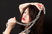 image of sado-masochism  - beautiful young woman with a chain around his neck on a black background