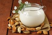foto of milk glass  - almond milk in a glass jug with whole nuts - JPG