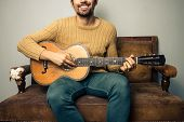 Happy Young Man Playing Guitar On Old Sofa
