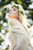 blonde beautiful young woman summer portrait with wreath of flowers in hair outdoor shot