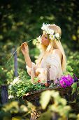 young blonde woman smelling flower and hold basket of  flowers in hand outdoor summer day