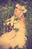 beautiful blonde woman with wreath of flowers summer day in a field, retro colors